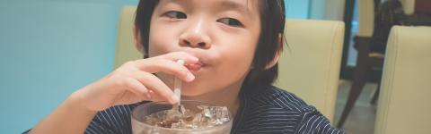 child drinking a soda in a restaurant